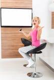 Mujer que mira la emoción negativa de la TV asustada Foto de archivo libre de regalías