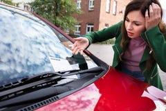 Mujer que mira la multa del boleto para la violaci?n del aparcamiento en el coche fotos de archivo