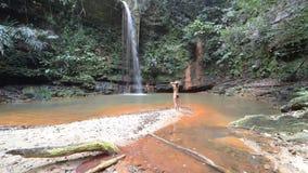 Mujer que mira la piscina natural multicolora con la cascada escénica en la selva tropical de las colinas parque nacional, Borneo almacen de video