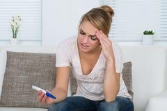 Mujer que mira la prueba de embarazo mientras que se sienta en el sofá foto de archivo