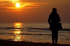 Mujer que mira la puesta del sol Foto de archivo libre de regalías