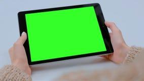 Mujer que mira la tableta con la pantalla verde en caf? almacen de video