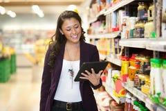Mujer que mira la tablilla digital en almacén de las compras Foto de archivo