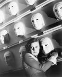 Mujer que mira la tenencia asustada sobre una máscara en la pared de máscaras (todas las personas representadas no son un ningún  fotos de archivo libres de regalías