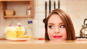 Mujer que mira la torta dulce deliciosa glotonería imágenes de archivo libres de regalías