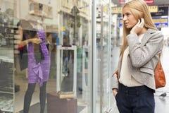 Mujer que mira la ventana en calle shoping Imágenes de archivo libres de regalías