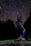 Mujer que mira las estrellas con el faro que destella Foto de archivo libre de regalías