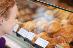 Mujer que mira los panes en gabinete de exhibición imágenes de archivo libres de regalías