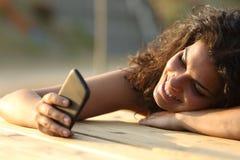 Mujer que mira medios sociales en un teléfono elegante en la puesta del sol Fotografía de archivo