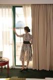 Mujer que mira nuestra de ventanas fotos de archivo