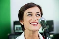 Mujer que mira para arriba mientras que canta en el estudio de grabación imagen de archivo libre de regalías