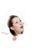 Mujer que mira para arriba a través del agujero en papel Imagen de archivo libre de regalías