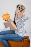 Mujer que mira Piggybank mientras que se sienta en la maleta en cama Imagen de archivo
