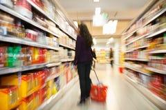 Mujer que mira productos en almacén de las compras imagenes de archivo