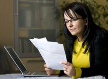 Mujer que mira sobre papeleo Imágenes de archivo libres de regalías