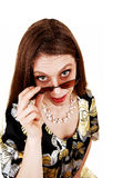 Mujer que mira sobre sus gafas de sol. Fotos de archivo