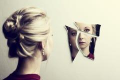 Mujer que mira su cara en tres cascos de espejo quebrado fotografía de archivo