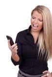 Mujer que mira su móvil en la frustración imagenes de archivo