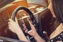 Mujer que mira su smartphone mientras que conduce un coche en un día soleado Foto de archivo