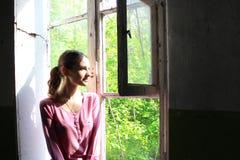 Mujer que mira a través de la ventana vieja Fotografía de archivo