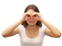 Mujer que mira a través de los dedos Fotos de archivo