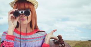 Mujer que mira a través de los prismáticos contra fondo del paisaje Foto de archivo