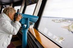 Mujer que mira a través de los prismáticos de la torre de Nasinneula Foto de archivo
