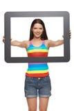 Mujer que mira a través de marco de la tableta Imagenes de archivo
