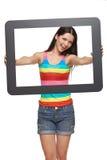 Mujer que mira a través de marco de la tableta Foto de archivo libre de regalías