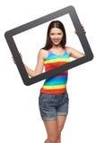 Mujer que mira a través de marco de la tableta Fotos de archivo