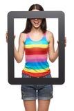 Mujer que mira a través de marco de la tableta Imagen de archivo