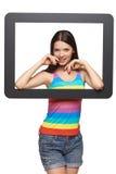 Mujer que mira a través de marco de la tableta Imagen de archivo libre de regalías