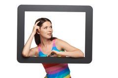 Mujer que mira a través de marco de la tableta Fotos de archivo libres de regalías