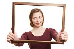 Mujer que mira a través de marco vacío Foto de archivo libre de regalías