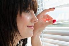 Mujer que mira a través de persiana fotos de archivo libres de regalías