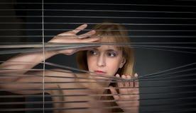 Mujer que mira a través de persianas de ventana. imagen de archivo