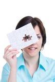 Mujer que mira a través de un pedazo que falta de rompecabezas fotos de archivo