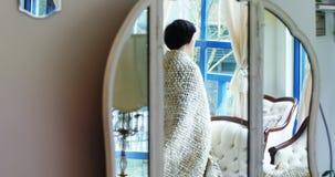 Mujer que mira a través de ventana en sala de estar almacen de video