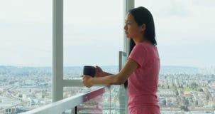 Mujer que mira a través de ventana mientras que comiendo la taza del café 4k almacen de metraje de vídeo