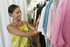 Mujer que mira a través del estante de la ropa en tienda imagenes de archivo