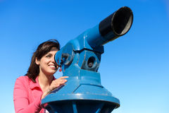 Mujer que mira a través del telescopio Foto de archivo libre de regalías