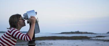 Mujer que mira a través del telescopio la playa Fotos de archivo libres de regalías