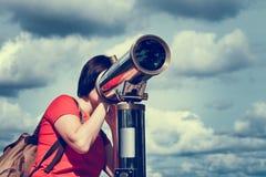 Mujer que mira a través del telescopio turístico Foto de archivo libre de regalías