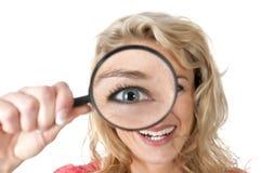 Mujer que mira a través de una lupa con el ojo grande Imagen de archivo