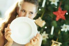 Mujer que mira a un lado mientras que oculta detrás de la placa de cena de servicio fotografía de archivo libre de regalías