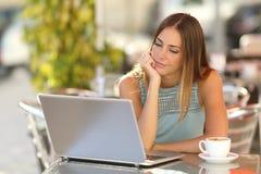Mujer que mira un ordenador portátil en un restaurante Imágenes de archivo libres de regalías