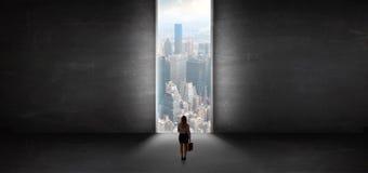 Mujer que mira a un paisaje urbano de un cuarto vac?o oscuro imagen de archivo