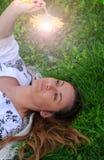 Mujer que mira una flor brillante en el prado Imagenes de archivo
