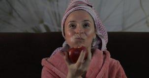Mujer que mira una pel?cula de ?ltima hora en la TV, comiendo una manzana Albornoz, m?scara facial foto de archivo