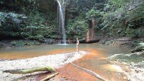 Mujer que mira una piscina natural multicolora imponente con la cascada escénica en la selva tropical del parque nacional de las  almacen de video